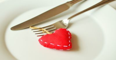 a stuffed fabric heart on a white plate with a fork and knife