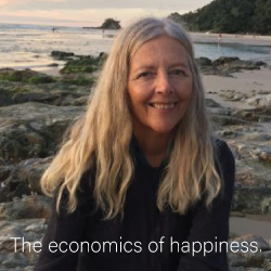 portrait of Helena Norberg-Hodge against a beach shore with the text THE ECONOMICS OF HAPPINESS