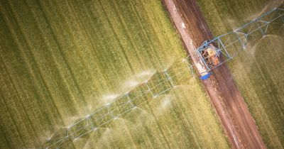 overhead aerial view of farm machinery on a crop field spraying herbicides