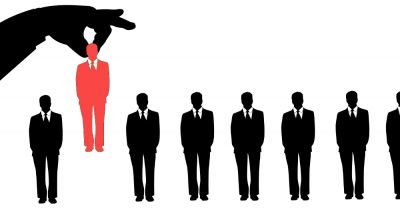 line of silhouettes of businessmen with a hand picking up a red silhouetted businessman