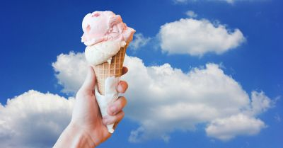 scoop of ice cream in a waffle cone against a partly sunny sky