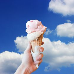 ice cream in a waffle cone against blue sky with clouds