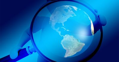 Person holding a magnifying glass over blue earth
