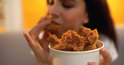 Person eating fried chicken.