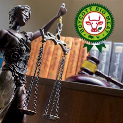 statue of lady justice in front of a stack of law books and a judges gavel wih the Boycott Big Meat logo
