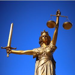 gold statue of Lady Justice with a sword scales and blindfold