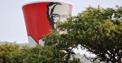 landscape and trees slightly covering a Kentucky Fried Chicken bucket sign