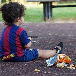 child in red and blue striped shirt sitting on the ground eating junk food potato chips