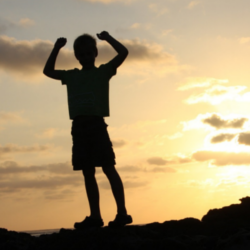 kid standing on rock with hands in air