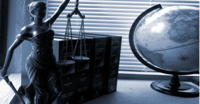 statue of blind lady justice next to several law books and a globe