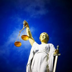 statue of lady justice with eyes closed and set of golden scales