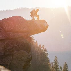 Man climbing large cliff face in bright sunlight