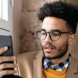 man in black glasses reading of a phone