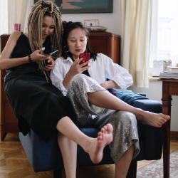 two women reading off their cell phones in a living room