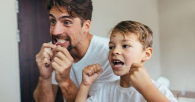 man and boy flossing their teeth with dental floss while looking in a mirror