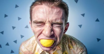 man eating a sour lemon and wincing