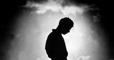 man bowing his head in remembrance