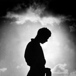 silhouette of a man bowing his head in remembrance