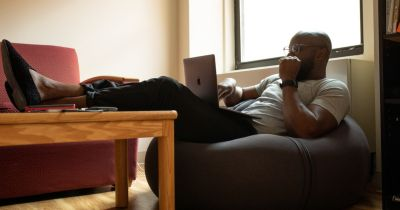 man sitting on a beanbag chair at a coffee table near a window