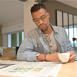man reading a newspaper at a table with a cup of coffee