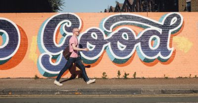 man walking down a sidewalk next to a painted brick wall that says GOOD