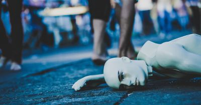mannequin lying broken on the ground while people walk by