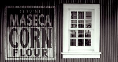 sign for Maseca brand corn flour on the corrugated siding of a building by a white window