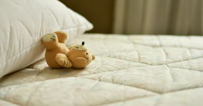 teddy bear laying on a mattress and pillow