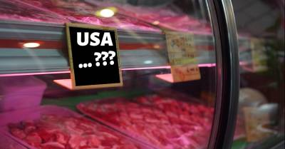 raw meat for sale at a grocery counter with a sign reading USA...???