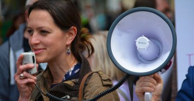 woman at a protest march with a megaphone loud speaker