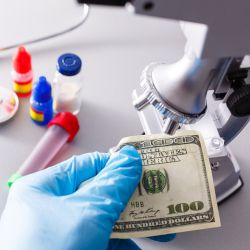 scientist in a laboratory with a microscope while handling a hundred dollar bill