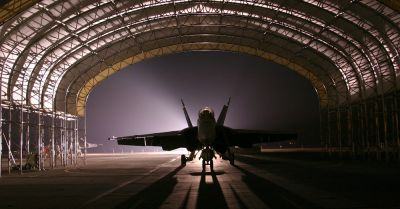 military jet in a dark and shadowy hangar