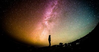 Silhouette of person looking up at Milky Way