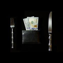 knife and fork surrounding a wallet with cash