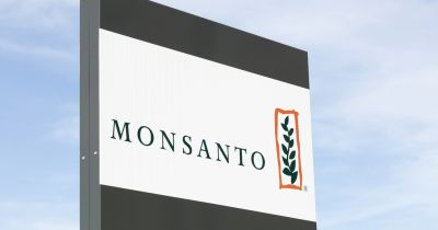 Monsanto logo on a sign against a cloudy blue sky