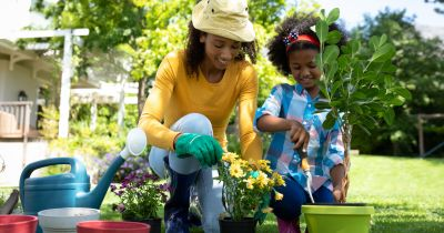 mother and daughter gardening in container pots planting plants