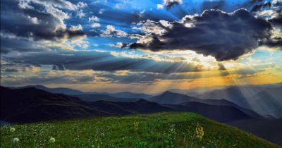 landscape view of a mountain range by a meadow at sunset with a cloudy sky