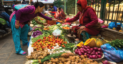 Woman selling produce at a farmers market.