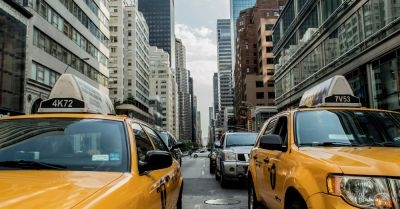 two yellow taxi cabs near New York City skyscrapers