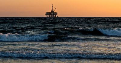 oil rig drilling just of the beach in the ocean
