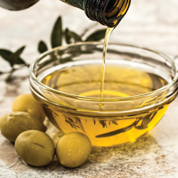 A bottle of olive oil being poured into a bowl