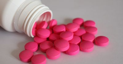 pink painkiller pills falling out of a white medicine bottle