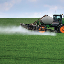 tractor on a farm crop field spraying a pesticide on the plants