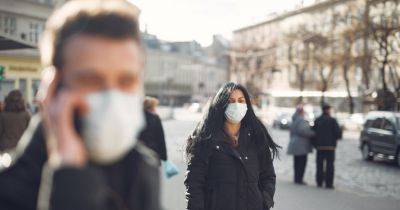 two people in a city street wearing face masks