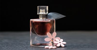 small plastic figures and pink flowers surrounding a glass perfume bottle