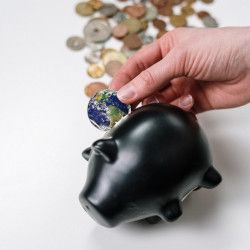 person putting a coin in the shape of the planet earth into a black piggy bank
