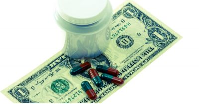 medicine bottle and pharmaceutical pills lying on a dollar bill