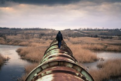 Person walking atop a rusty, old pipeline on a stormy day