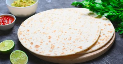plain four tortillas in a stack on a black table with lime and cilantro