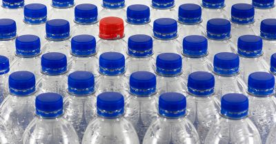 Rows of plastic water bottles with blue plastic lids and one red lid